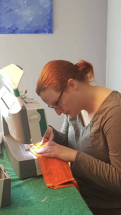 Law Clerk Sarah Tomlinson at home sewing a face mask to help homeless veterans.