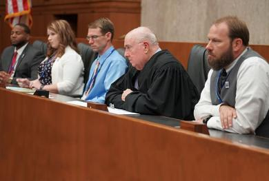 A federal judge shares the bench with teachers during a courtroom simulation.