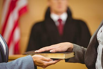 image of a court employee holding the bible for someone ready to take the witness stand