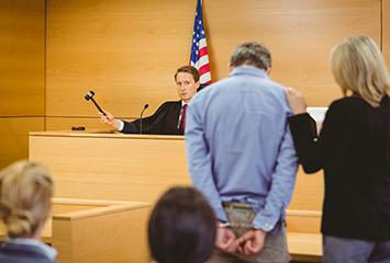 image of a man being represented by a female court appointed employee in front of a judge