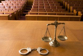 image of handcuffs and scales of justice on a court bench