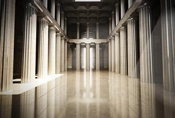 An image of columns inside of a building leading to doors at the end of the hallway.