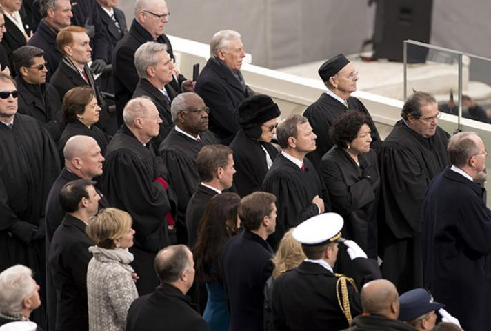 Members of the U.S. Supreme Court stand during ceremony.