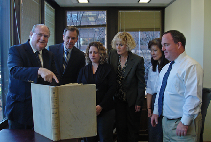 Michael Kunz, left, Clerk of the Eastern District of Pennsylvania, points to a book with handwritten docket entries that he worked with in the early 1960s. Kunz was among the federal courts' pioneers in adopting the online PACER information service. With