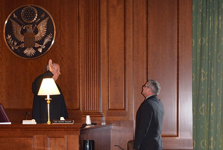 Judge Castel swears in a witness in a dimly lit courtroom. Small table lamps provided the necessary light to conduct proceedings during the week of the storm.