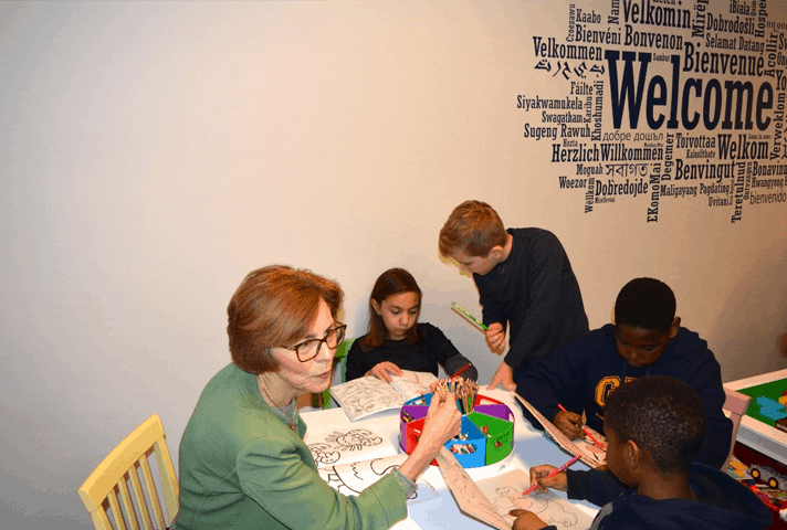 Chief Judge Rebecca R. Pallmeyer joins youngsters at a table with coloring books.