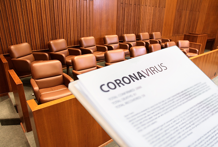 Image of a courtroom with someone holding a piece of paper with the word coronavirus printed.