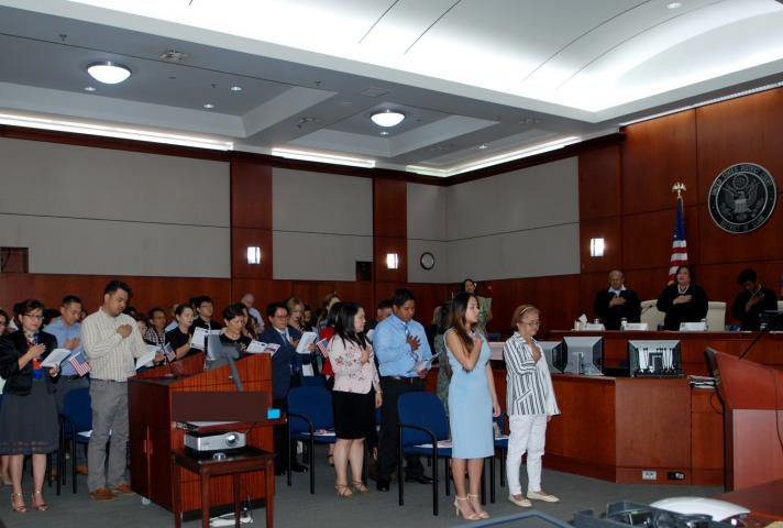 Naturalization ceremony attendees in Guam say the pledge of allegiance.