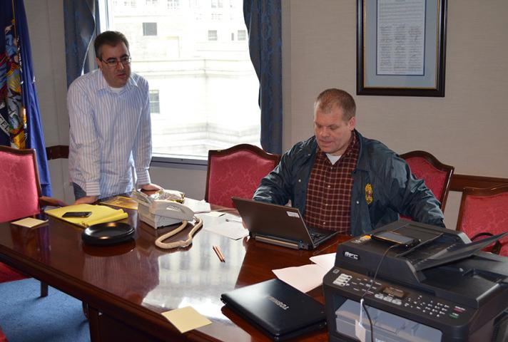 District Court Executive Edward A. Friedland and Chief Probation Officer Michael Fitzpatrick work in a makeshift command center to alert employees and jurors about court closures and restoring courthouse operations.