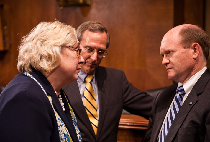 Sen. Chris Coons, right, confers with Judge Julia S. Gibbons and Judge John D. Bates, Director of the Administrative Office of the U.S. Courts.