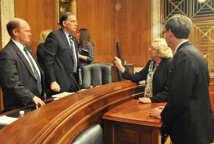 Judge Julia S. Gibbons, Budget Committee chair, speaks with Sen. Chris Coons (D-Del.), left, and Sen. John Boozman (R-Ark.). They are, respectively, ranking minority member and chair of the Senate Appropriations Subcommittee on Financial Services and Gene