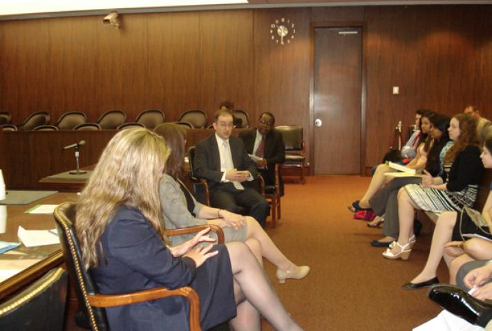 Image of public defenders speaking to teens in a courtroom