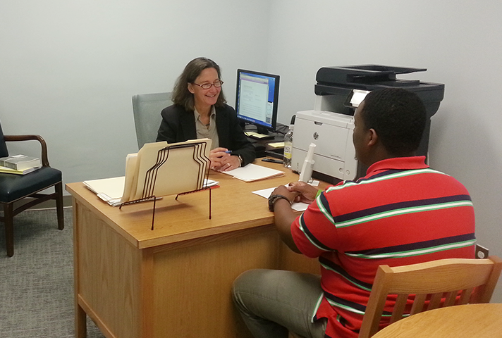 Center director Nancy Rosenbloom helps a pro se litigant in an office in the Eastern District of New York federal courthouse in Brooklyn.