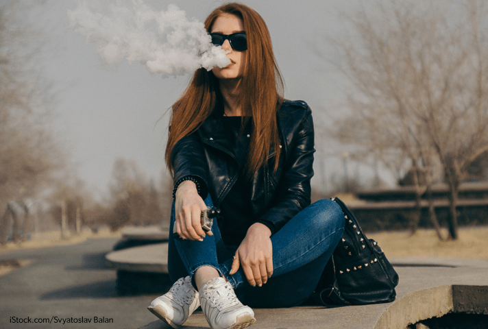 Image of a female student using a vaping device.