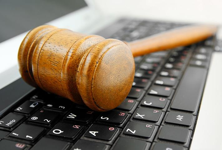 Image of a gavel laying on a laptop keyboard.