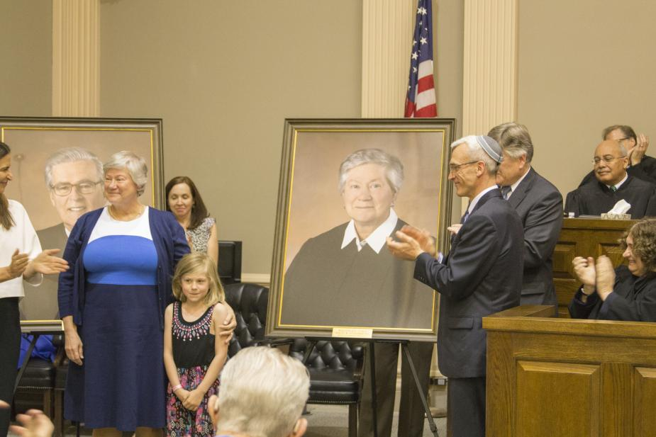 Retired Judge Holly B. Fitzsimmons and her granddaughter stand beside her portrait presented by Alyssa Esposito, a former law clerk for Judge Fitzsimmons, and James Ross Smart Esq. and Patrick A. Klingman Esq., Co-Chairs of the Federal Practice Section at
