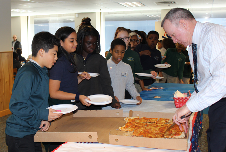 In Hartford, Connecticut, Tom Ring, law clerk to Senior District Judge Dominic J. Squatrito, hands out pizza to students of the Robert J. O'Brien STEM Academy.