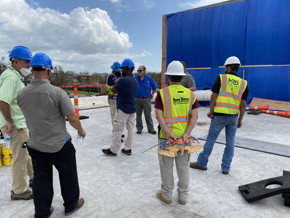 "Chief Judge S. Maurice ""Maury"" Hicks (center, in blue shirt) inspects the roof of the Lake Charles courthouse."