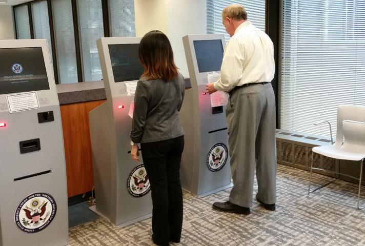 Jurors demonstrate the check-in process on new jury kiosks