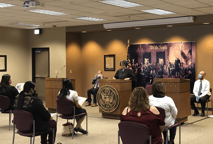 Chief Judge Julie A. Robinson, of the District of Kansas, speaks to immigrants at a naturalization ceremony.