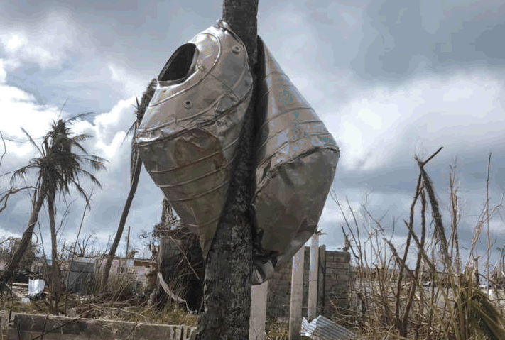 A water catchment tank was swept up by the forceful winds of Super Typhoon Yutu and crushed around a coconut tree not far from the courthouse in the Northern Mariana Islands.