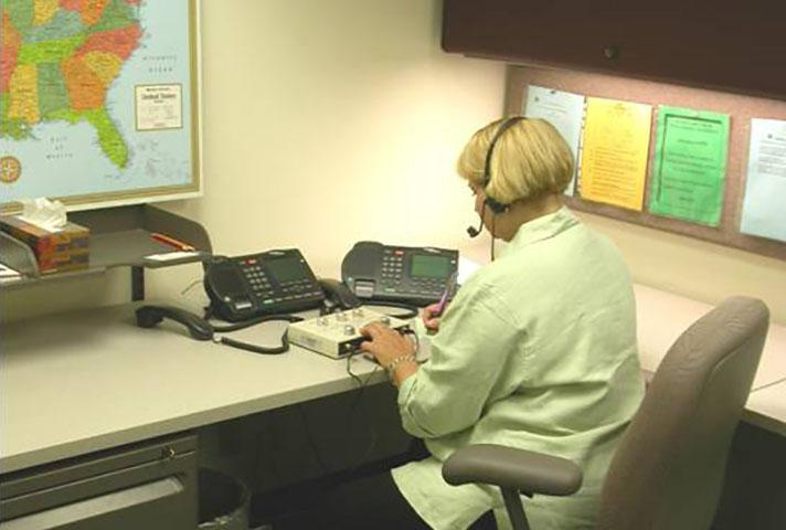 An interpreter provides language services remotely during a short court proceeding.