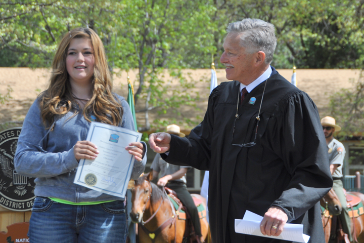 Michael J. Seng, a magistrate judge based within Yosemite National Park, congratulates essay contest winner Lilly Lessley.
