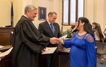 Senior Judge D. Brock Hornby gives a certificate of citizenship.