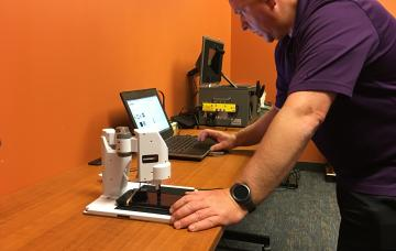 Senior Probation Officer Steve Holmes programs a robotic arm to try to crack a passcode on a locked mobile device at the Eastern District of Missouri's National Forensic Laboratory.