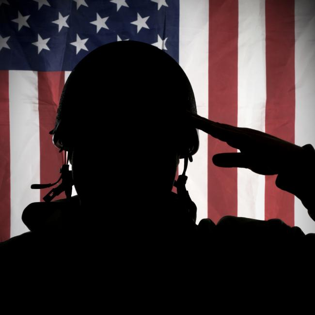 Image of a soldier Saluting the American Flag